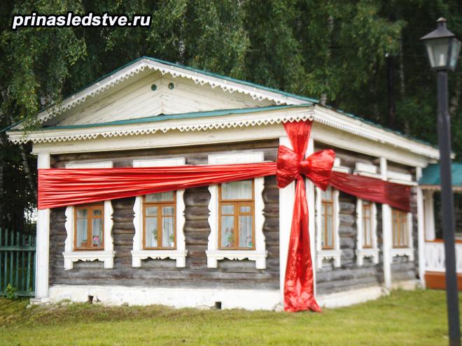 Деревенская изба, украшенная бантом