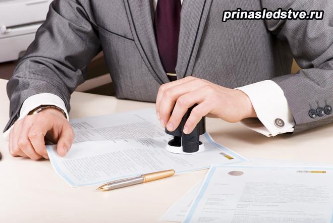 Мужчина ставит печать на документах