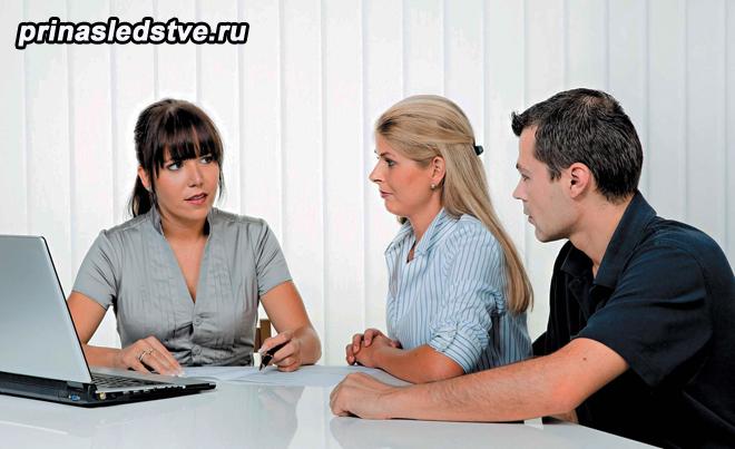 Женщина за ноутбуком, рядом сидят мужчина и женщина