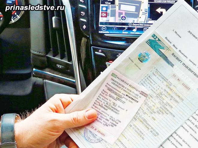 Человек держит в руках документы на машину