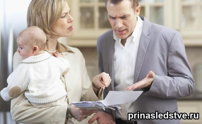 Мама держит ребенка и разбирается в бумагах со стоящим рядом мужчиной