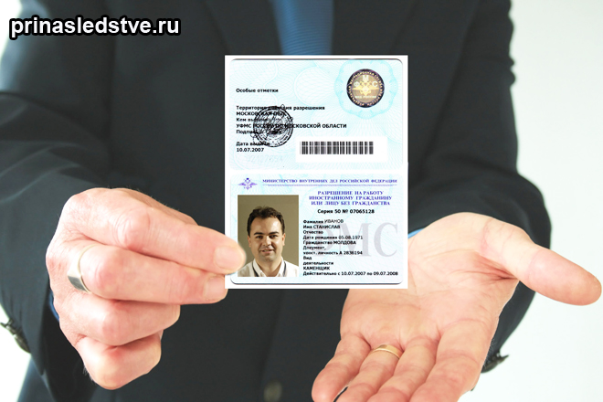 Человек жержит документ со своей фотографией