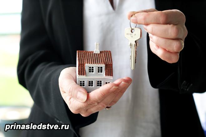 Мужчина держит ключи и игрушечный домик