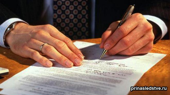 Мужчина в деловом костюме расписывается в бумаге