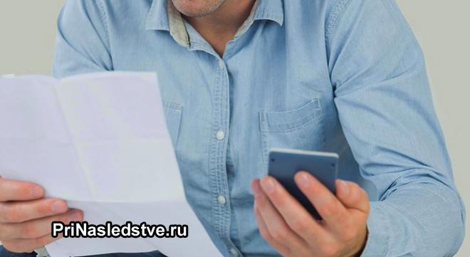 Мужчина в джинсовой рубашке держит в руках листок бумаги