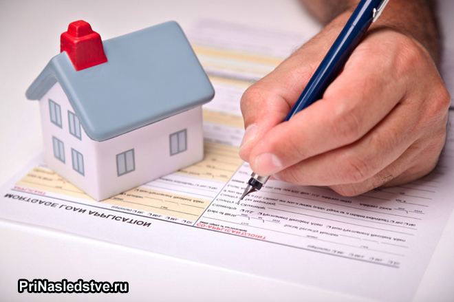 Мужчина подписывает документы на квартиру