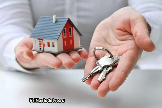 Бизнесмен держит в одной руке ключи от дома, в другой игрушечный домик