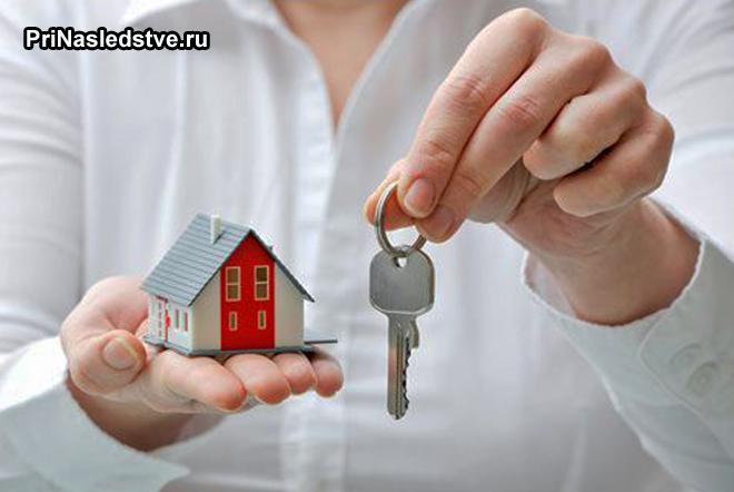 Девушка с белой рубашке держит ключи и игрушечный домик
