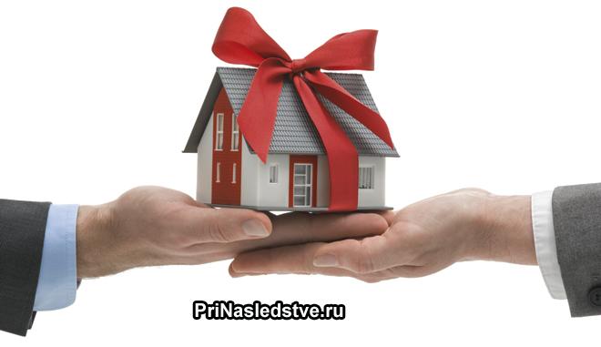 Игрушечный домик с красным бантом передают из рук в руки