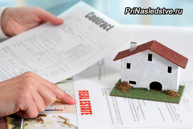 Человек читает документы на землю и дачный домик