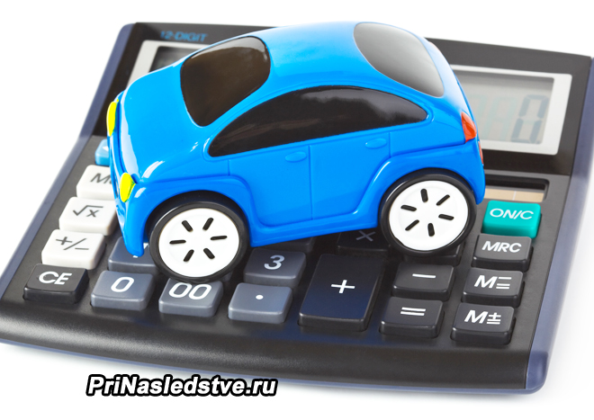 Игрушечная синяя машинка стоит на калькуляторе