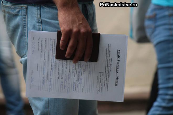 Мужчина держит в руке паспорт и бланк документа