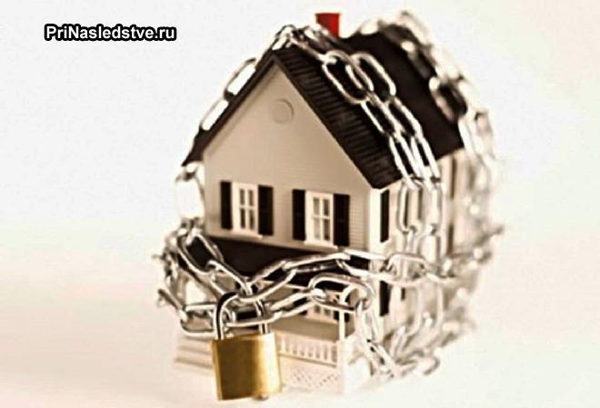 Игрушечный домик, закованный цепью с замком
