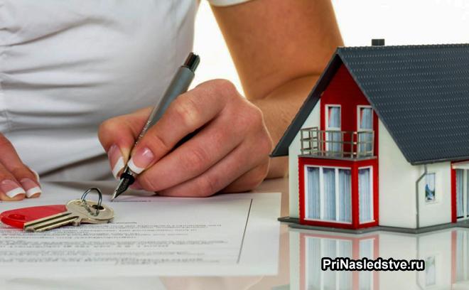 Девушка подписывает документы, рядом стоит игрушечный домик