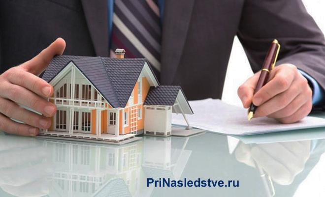 Бизнесмен оформляет документы, рядом стоит игрушечный домик