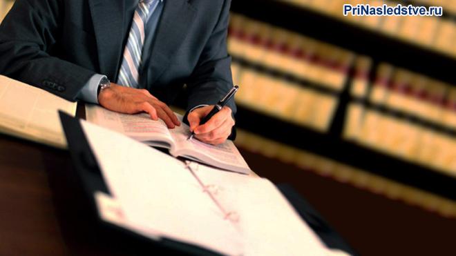 Бизнесмен делает записи в тетрадь в библиотеке