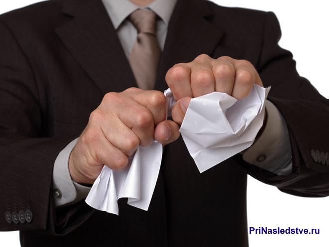 Мужчина в деловом костюме комкает лист бумаги