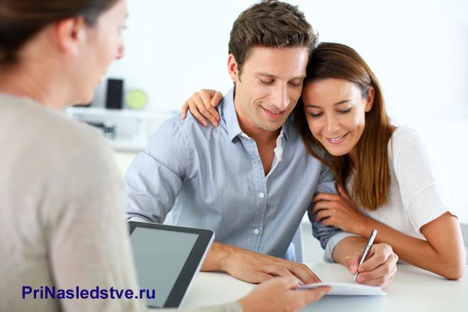 Молодая семейная пара оформляет сделку