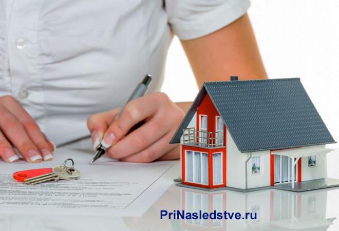 Женщина подписывает договор, рядом стоит макет частного дома