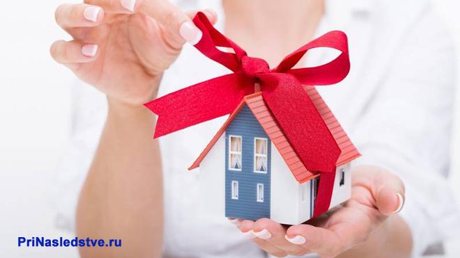 Женщина держит игрушечный домик с красным бантом