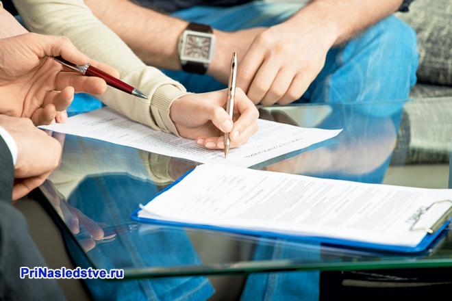 Девушка и мужчина подписывают документы на столе