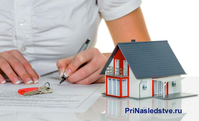 Девушка подписывает документ, рядом стоит макет дома
