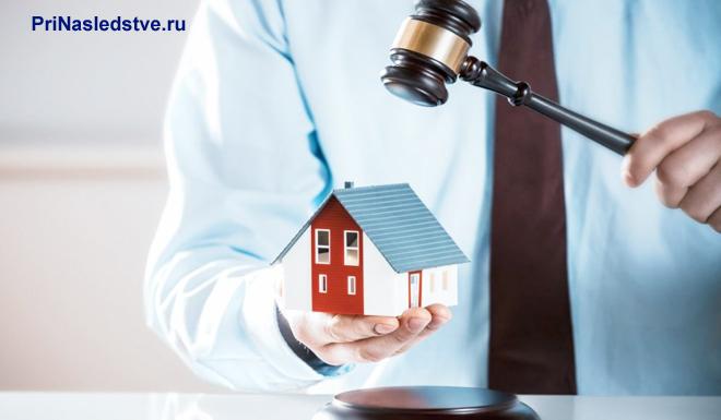 Мужчина в голубой рубашке держит в руках макет частного дома и молоточек судьи