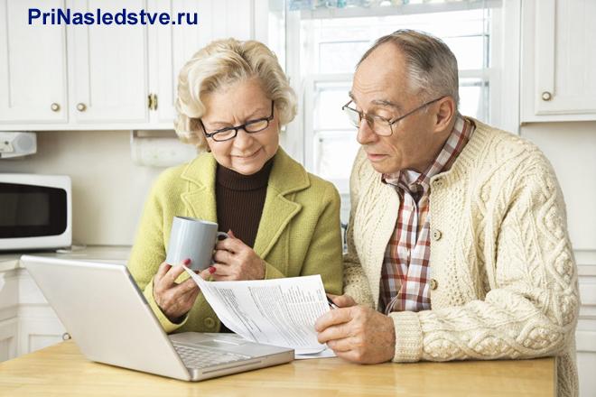 Пенсионеры сидят на кухне с ноутбуком