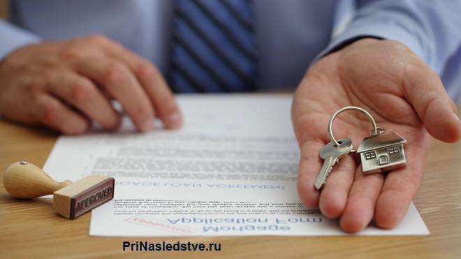 Бизнесмен держит в руке ключи от квартиры, рядом лежит договор