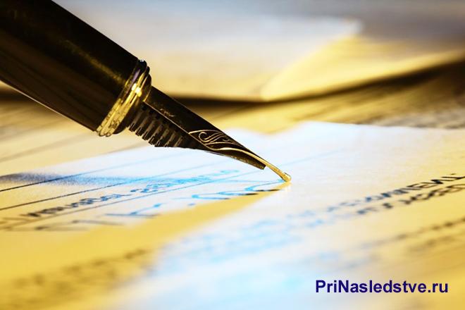 Пером ручки пишут на листе бумаги