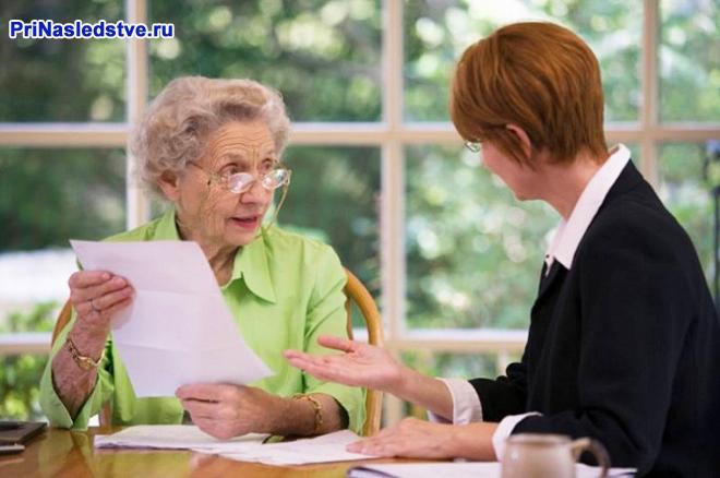 Пожилая женщина держит документы в руках, рядом сидит женщина в деловом костюме