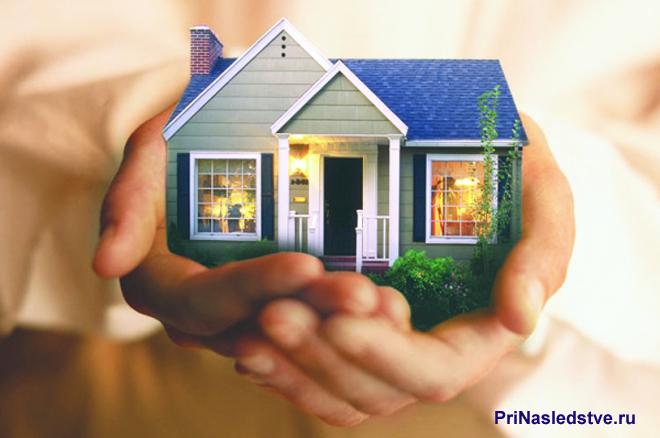 Девушка держит в руках домик, в котором горит свет