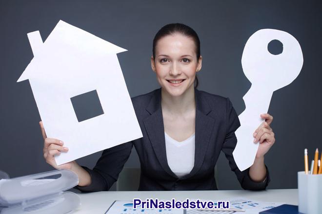 Девушка держит в руках бумажный домик и ключ
