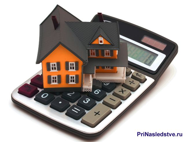 Дом с черной крышей стоит на клавишах калькулятора