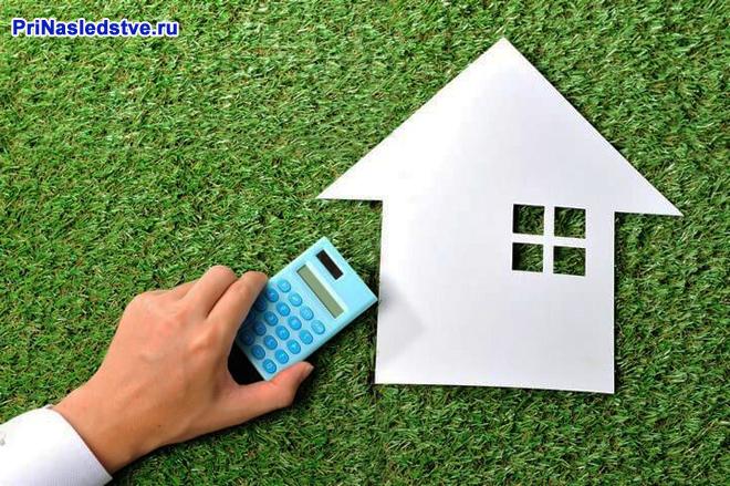 Калькулятор, бумажный домик на газоне