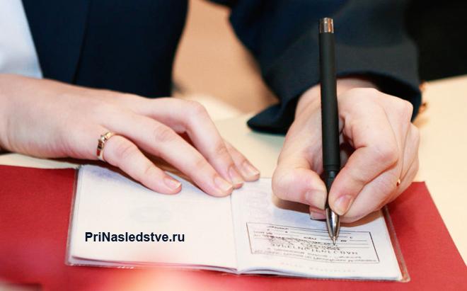 Девушка заполняет в паспорте страничку с регистрацией