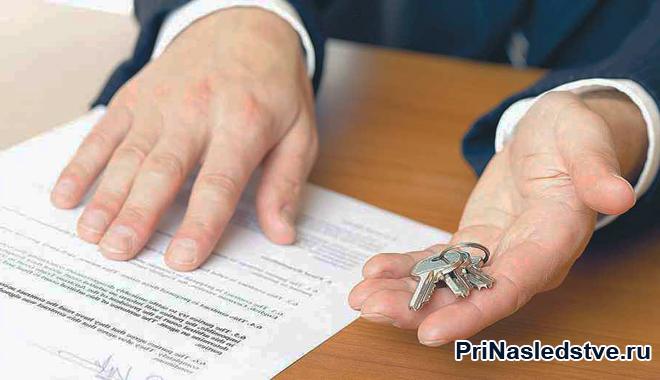 Мужчина держит в руке ключи, рядом лежат документы
