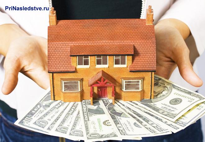 Человек держит в руках кирипичный домик с красной крышей и веер из денег