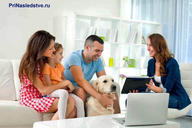 Семья сидит в гостиной на диване с собакой, рядом сидит женщина с планшетом