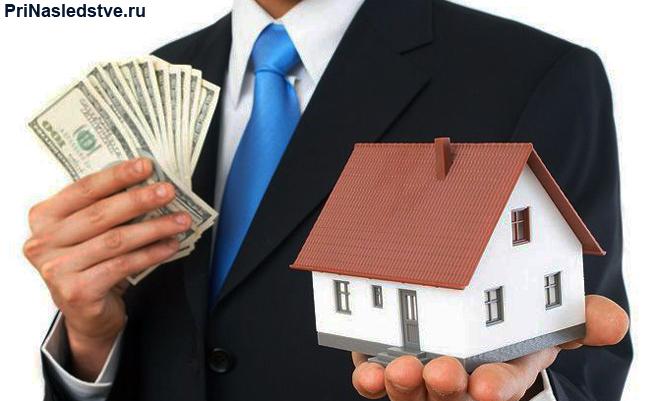 Бизнесмен держит в руках деньги и игрушечный домик