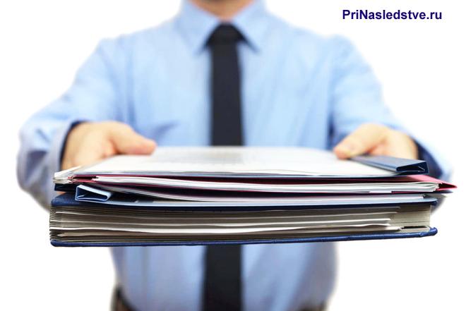Мужчина в голубой рубашке и галстуке держит перед собой пачку с документами
