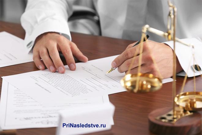 Бизнесмен подписывает документ за своим рабочим местом