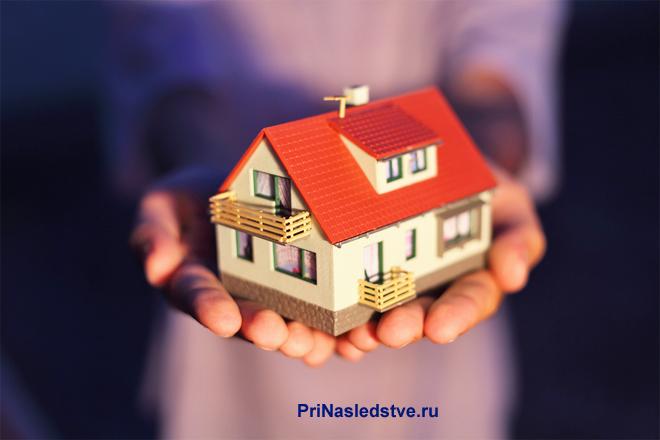 Девушка держит в руке домик с красной крышей