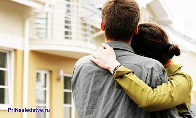 Молодая парочка, обнявшись, смотрит на желтый дом