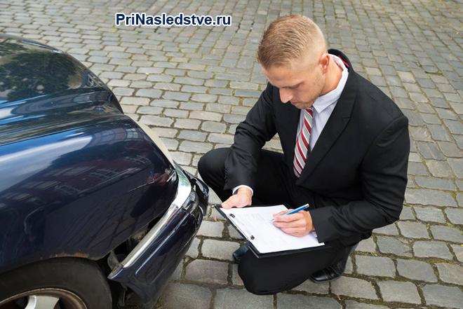 Оценщик осматривает машину