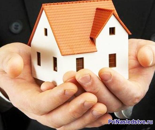 Мужчина держит в руках белый домик с красной крышей