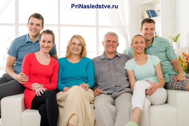 Счастливая семья сидит на диване в зале