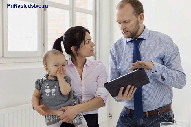 Девушка держит ребенка на руках и разговаривает с мужчиной в рубашке