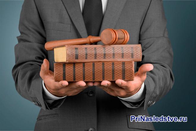 Бизнесмен держит в руках книги и молоточек судьи