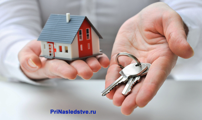 Бизнесмен держит в руках ключи и макет частного дома